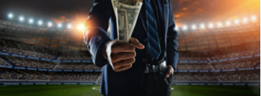 man in a suit holding a fistful of dollars with a soccer stadium in the background